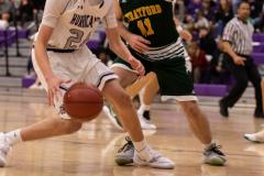 Varsity basketball player Tyler Brown dribbles the ball away. Photo by: Tyler Grosvenor